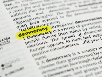 "Detail of the english word ""democracy""  highlighted and its definition from the dictionary"